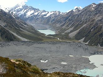 Mueller Glacier - Mueller glacier (under rubble) and its moraine (foreground). Aoraki/Mount Cook washed out in the background. The Hooker Glacier and its terminal lake are up the valley in the distance.