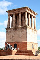 The Honoured Dead Memorial, a tall, brown sandstone building with multiple Grecian-type pillar and the Long Cecil gun at its base