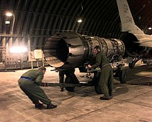 View of a jet engine being pushed up to the empty rear of an F-16