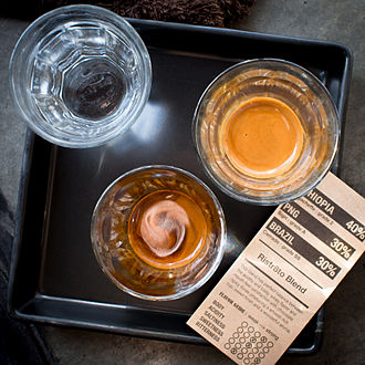 Ristretto - A double ristretto with the first half of the shot in the glass at the bottom of the image, and the second half in the glass on the right.
