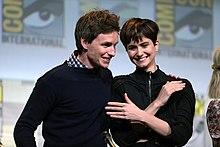 Un homme à gauche et une femme à droite, tous les deux aux cheveux courts et bruns, sont debout et penchés l'un vers l'autre en souriant. La femme, portant un pull noir, a ses bras en croix devant elle et l'homme, portant un pull bleu sombre, tient la femme par l'épaule.