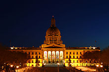 Provincial Legislature of Alberta lit up by exterior lighting during a winter night.