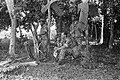 Een sectie KNIL-militairen in camouflage-uniform zitten in een bos, Bestanddeelnr 6449.jpg