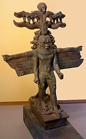Bronze statue of a bearded man with multiple arms, wings, horns, and several animal heads emerging from the sides of his head