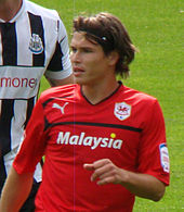 A young footballer, with long hair and in a red jersey, standing in front of his opponent during a football match between Cardiff City and Newcastle United.