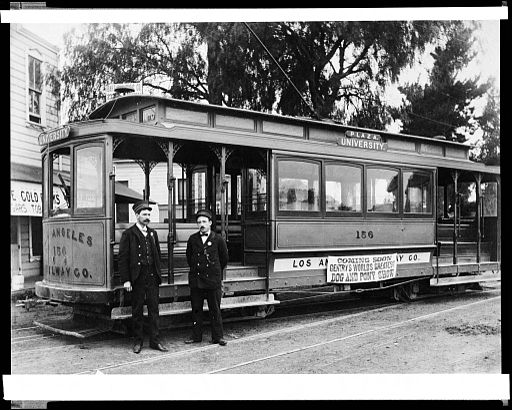 External view of a Plaza University trolley car of the Los Angeles Railway Company, showing two conductors posed in front, ca.1900-1910 (CHS-33085)