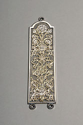 Silver fingerplate with a stylised flower design.