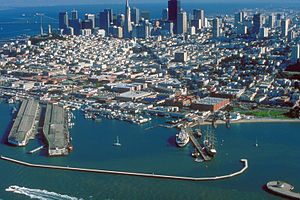 Fisherman's Wharf, San Francisco - Aerial view of San Francisco, looking south, with Fisherman's Wharf just left of center, directly above a lone sailboat