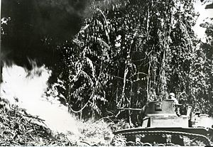 Flame tank - An M3 Stuart, fitted with a flamethrower, attacks a Japanese bunker during the Bougainville Campaign (April 1944)
