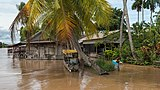 Flooded banks in the muddy water of the Mekong with a boy, rowing in a repurposed refrigerator raft, in Don Khon, Laos.jpg