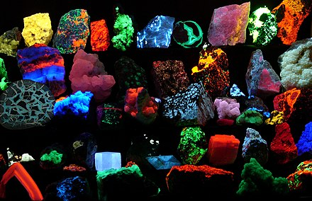 A collection of mineral samples brilliantly fluorescing at various wavelengths as seen while being irradiated by UV light. Fluorescent minerals hg.jpg