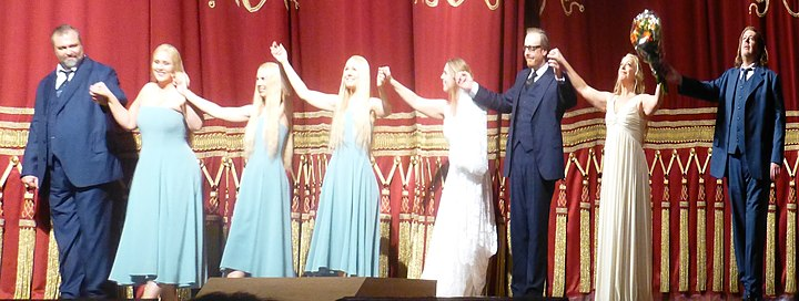 Modern costuming shown in closing bows following Gotterdammerung in 2013 at the Bavarian State Opera. Left to right: Gunther, the Rhinemaidens, Gutrune, Hagen, Brunnhilde, Siegfried Gotterdammerung.2013.jpeg