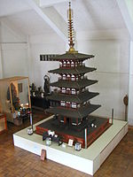 Wooden miniature five-storied pagoda with white walls.