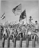Gaunt allied prisoners of war at Aomori camp near Yokohama cheer rescuers from U.S. Navy. Waving flags of the United... - NARA - 520992