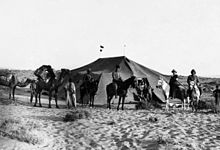 Photograph of desert tent, mounted soldiers and camels