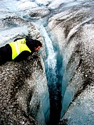 A crevasse created by water drilling a hole tens of meters deep into the glacier ice. Our skidoo guide inspects the crack. Langjökull glacier. July 2006.