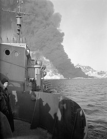 ship at sea with a column of black smoke rising from the mountainous land in the background