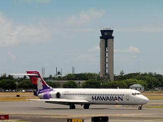 Daniel K. Inouye International Airport - A Hawaiian Airlines Boeing 717 taxing with the airport's control tower in the background