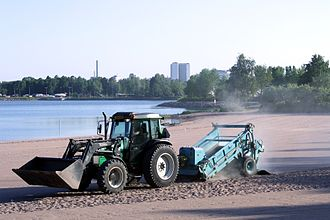 Sand cleaning machine - A tractor-pulled beach cleaner at Hietaniemi beach in Helsinki, Finland.