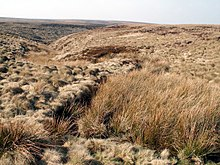 A small valley cuts through desolate moorland, under a blue sky