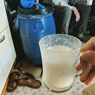 Kumis - A glass of homemade Mongolian airag, prepared in the blue plastic barrel in the background.