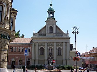 Széchenyi square (Pécs) - Church with Zsolnay well in front.