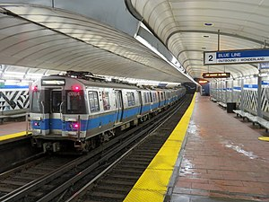 A subway train in an underground station with an arched roof