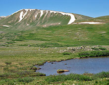 A grassy yet barren landscape with a small pond in the right foreground and distant ridgeline and mountains in the background
