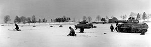 6th Armored Division (United States) - Members of the 44th Armored Infantry, supported by tanks of the 6th Armored Division, move in to attack German troops surrounding Bastogne. 31 December 1944
