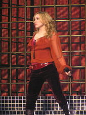 A blonde woman wearing a red shirt and dark pants is performing