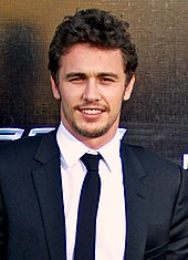 A head shot of James Franco, a caucasian male in his late-20s with dark hair, looking into the camera and smiles. He wears a black suit with a white shirt and black tie, and stands behind a black background.