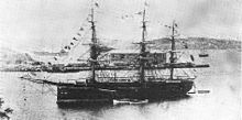Three-masted warship at anchor in a bay.