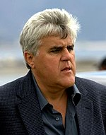 Jay Leno in a sports jacket, looking to his left