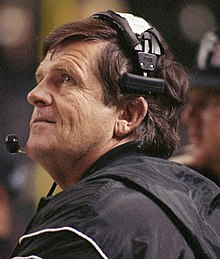Head shot of a coach with brown hair wearing a headset and black jacket.