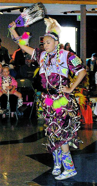 Jingle dress - Teenaged jingle dress competitor, with fan