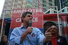 "A gray-haired man wearing a blue shirt and black campaign button speaks into a microphone at an outside political rally. A man and woman stand behind him, and a banner reading ""Employee Free Choice"" can be seen in the background."