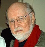 an old, boldheaded man with a two-day-old beard and glasses