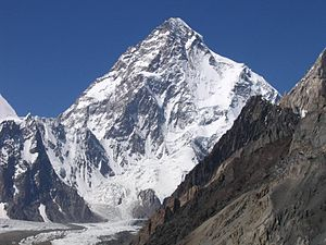 A large angular white mountain, with steeply sloped sides mostly covered with snow.
