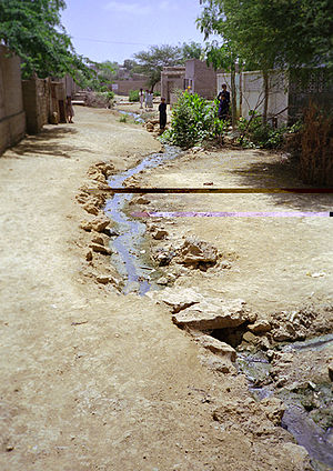 Poverty in Pakistan - A slum in Karachi, Pakistan with an open sewer running along the lane.