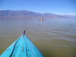 A man kayaking in a brown lake, mountains in the background, a kayak in the foreground