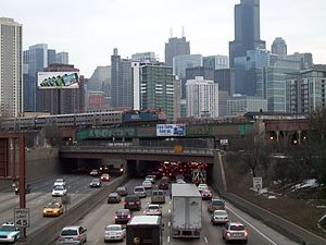 Kennedy Expressway - Sign over the Kennedy Expressway, at the north entrance to Hubbard's Cave, encouraging commuters to use Metra trains, such as one seen here passing over the highway, to avoid the common congestion