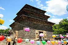 A huge three-story pagoda stands against blue skies. The pagoda is made with bricks of dark gray stone. Colorful lanterns are lined up.