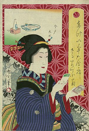 An older Japanese woman, holding cards.