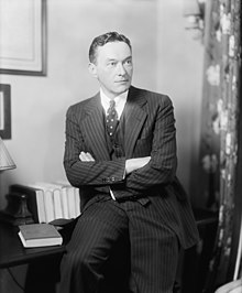 Lippmann wearing a suit, leaning against a desk with his arms crossed