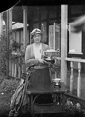 Lady holding a cup outside Llandrindod Wells Golf Club pavilion