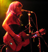 A female vocalist (wearing a strapless black dress) singing into a microphone on stage while playing guitar