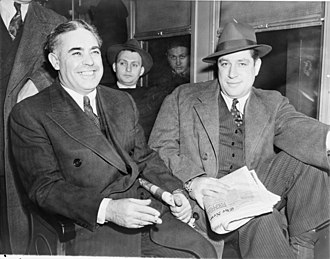 "Louis Capone - Smiling convicted killers Emanuel ""Mendy"" Weiss (right) and Louis Capone, surrounded by detectives, ride the New York Central railroad ""up the river"" to the Sing Sing prison death house on December 3, 1941, the day after receiving their sentences."