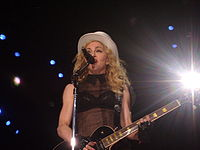 Picture of a middle-aged blond woman uptill the waiste, singing in front of a microphone. Her hair is in waves and falls up to her shoulders. She appears to be wearing a black bra covered with a sleeveless netted covering and wears a white hat on her head. There are black gloves on her hand and she plays an electric guitar. Behind her, to her left, a flood light is visible.