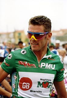 A cyclist wearing a green jersey.