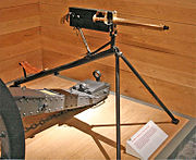 Brass barrelled gun with black coloured rear parts. On a tripod on a wooden plinth with a wood wall behind.